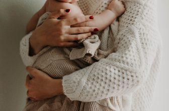 Mère tenant un enfant enroulé dans une couverture près de soi