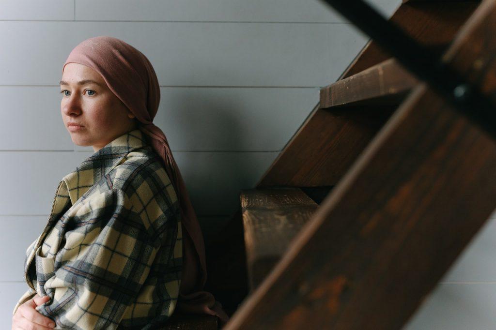 Femme assise dans des escaliers; portant un foulard