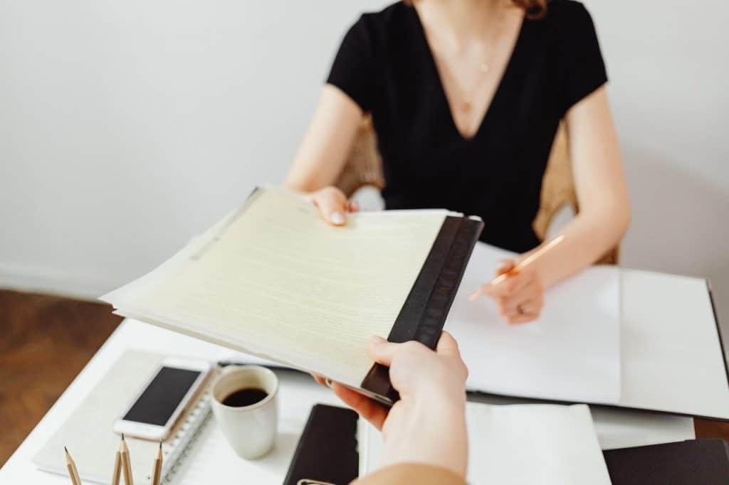 Personne donnant un dossier à une femme assise à un bureau