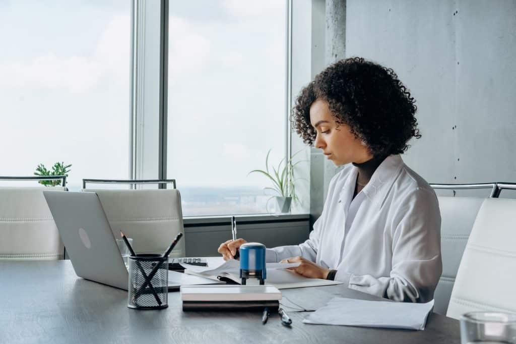 Femme devant un ordinateur travaillant et prenant des notes